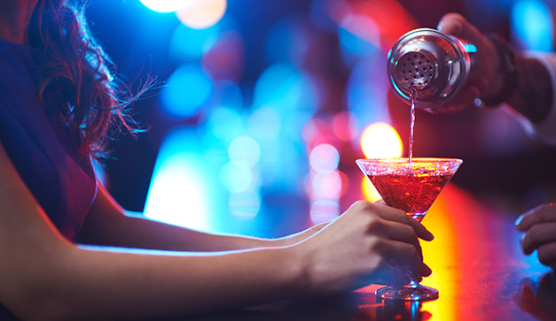 Young woman holding martini glass while barman pouring cocktail; Shutterstock ID 247060510; PO: Tragos solo_chi.com